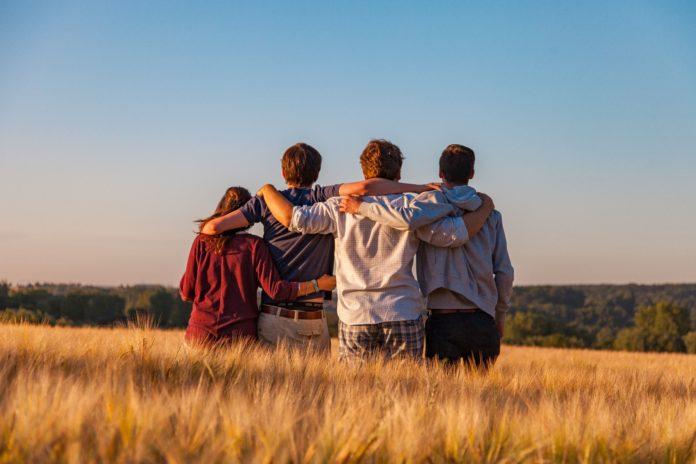 Jovens abraçados observando o campo.