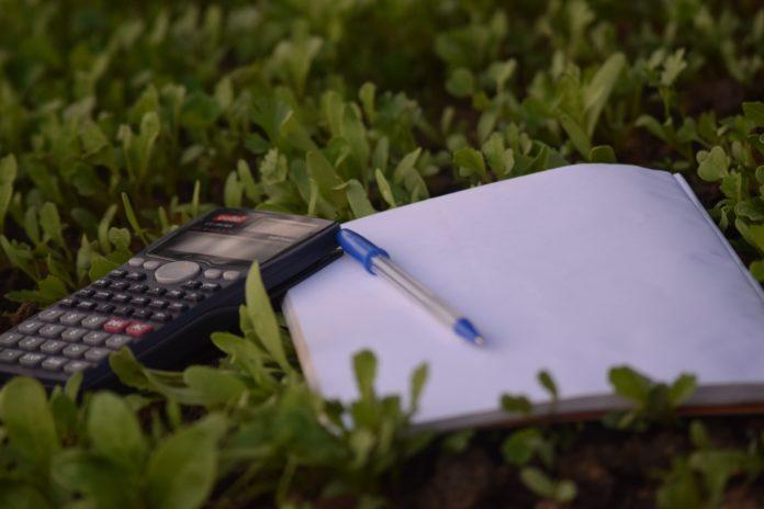 Calculadora, caderno e caneta na grama.