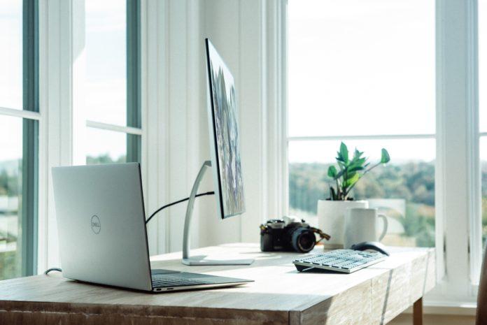 Mesa de trabalho com computador e máquina fotográfica